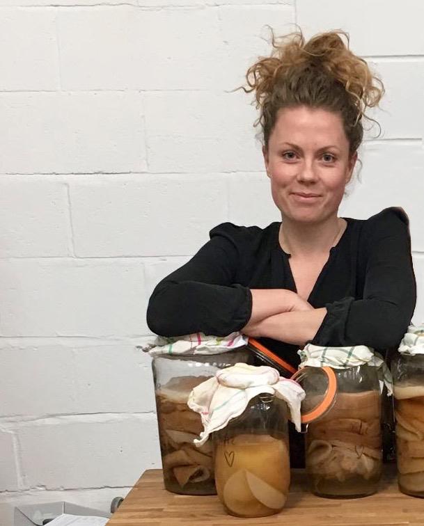 Gina_of_Wild_Fizz_Kombucha_standing_behind_jars_of_fermenting_kombucha_tea.jpg