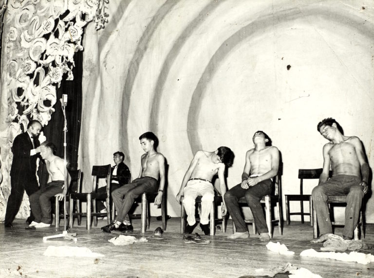 A hypnotist entrances several young men onstage, mid-20th century