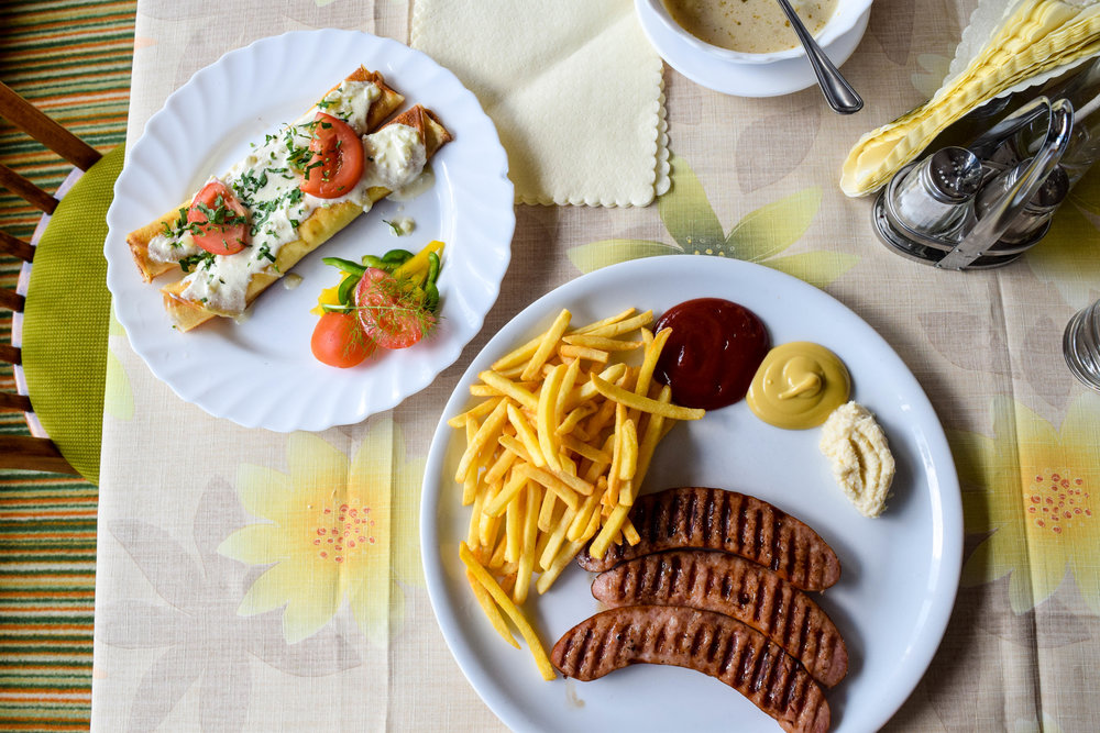 Kielbasa, frites and thin pancakes filled with cottage cheese at the restaurant in the mountains.
