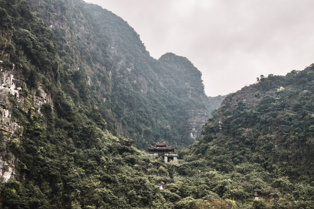 A temple nestled in the hills in Tam Coc, Ninh Binh province. Yes, that's a couple taking wedding pics.