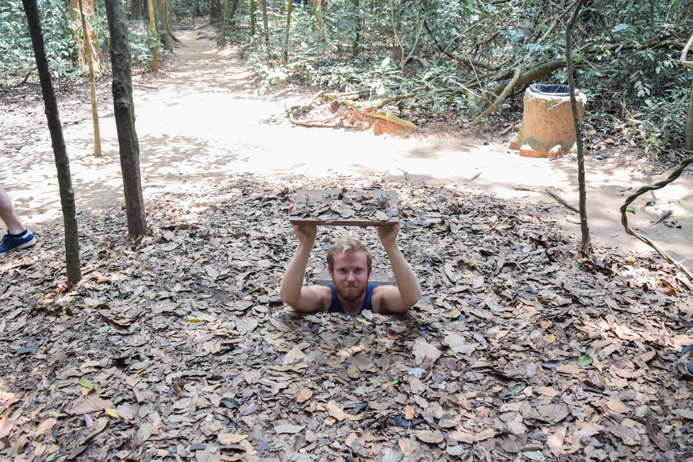 Alex braving the tight squeeze at the Cu Chi Tunnels. I wasn't bold enough to try my luck.