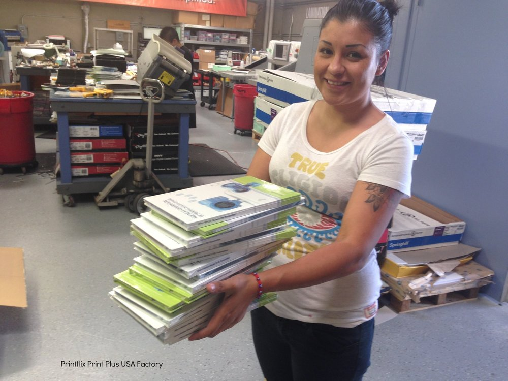 PRINT PLUS TEAM MEMBER WITH A STACK OF NEW VIDEO BOOKS
