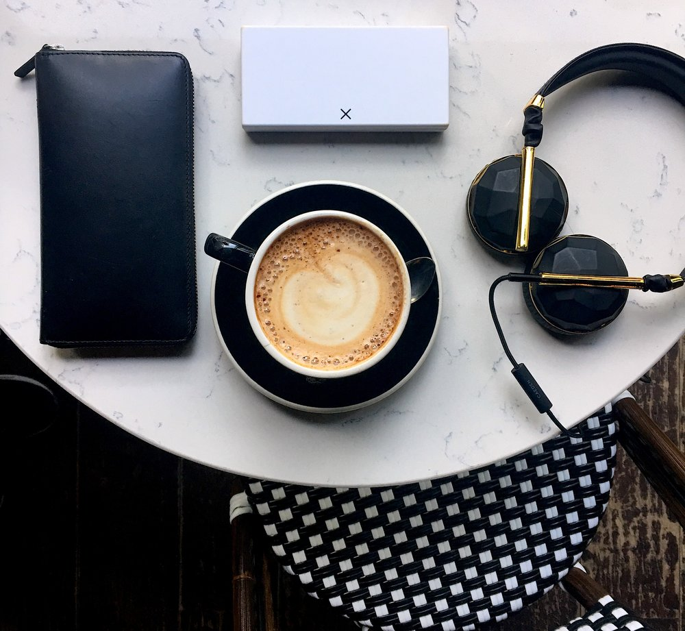White pillbox at coffee shop with headphones and purse