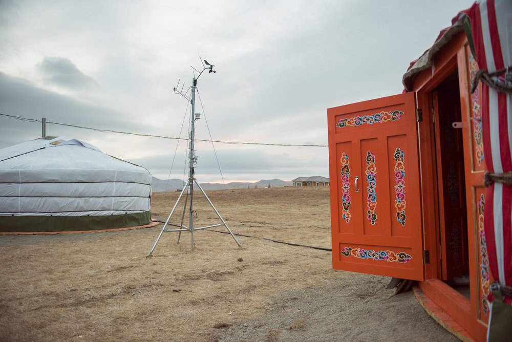 An ajar door with a ger and a weather station in the background.