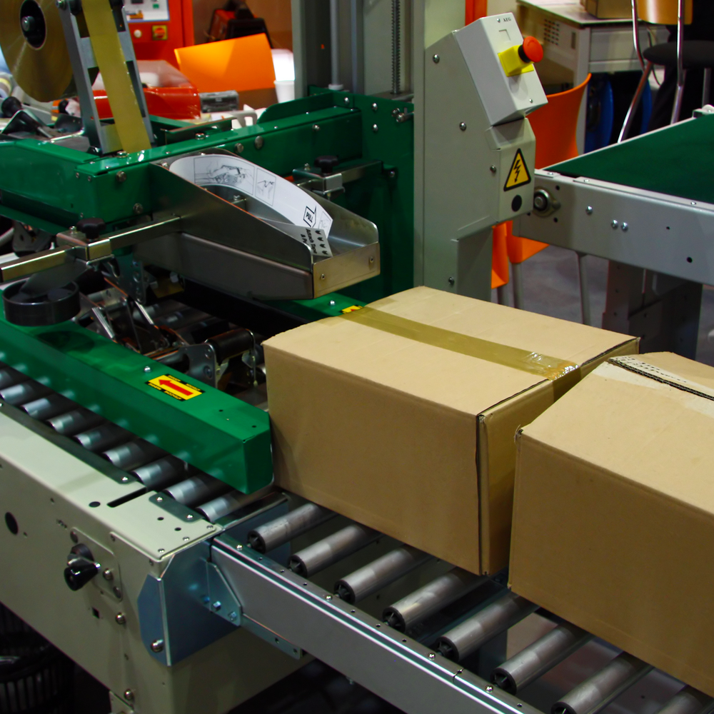 Cardboard packaging boxes leaving a green case sealer on a roller conveyor.