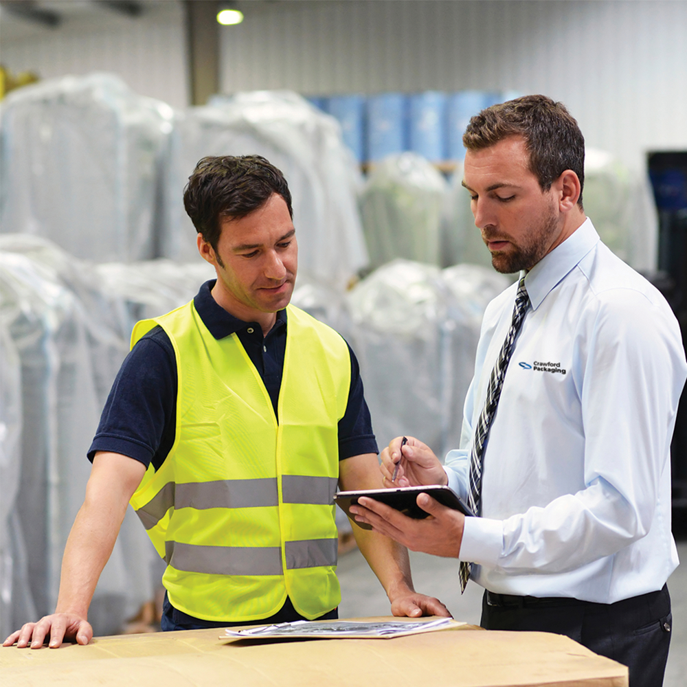 A Packaging Specialist talking with a customer in their warehouse discussing the packaging needs of eCommerce business.