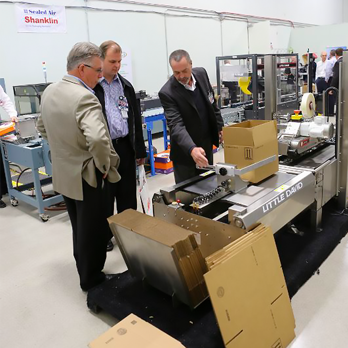 Packaging Specialist Peter Moroney (left) reviewing a carton erecting machine with Client at Packaging Show.