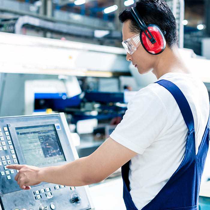 A Service Technician working on a packaging machine while wearing ear protection.