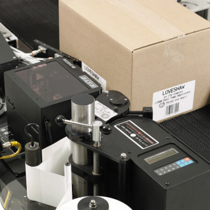 A print and apply label machine running on a packaging line.