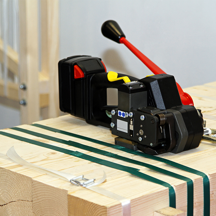 A hand held strapping machine being used to bundle lumber.