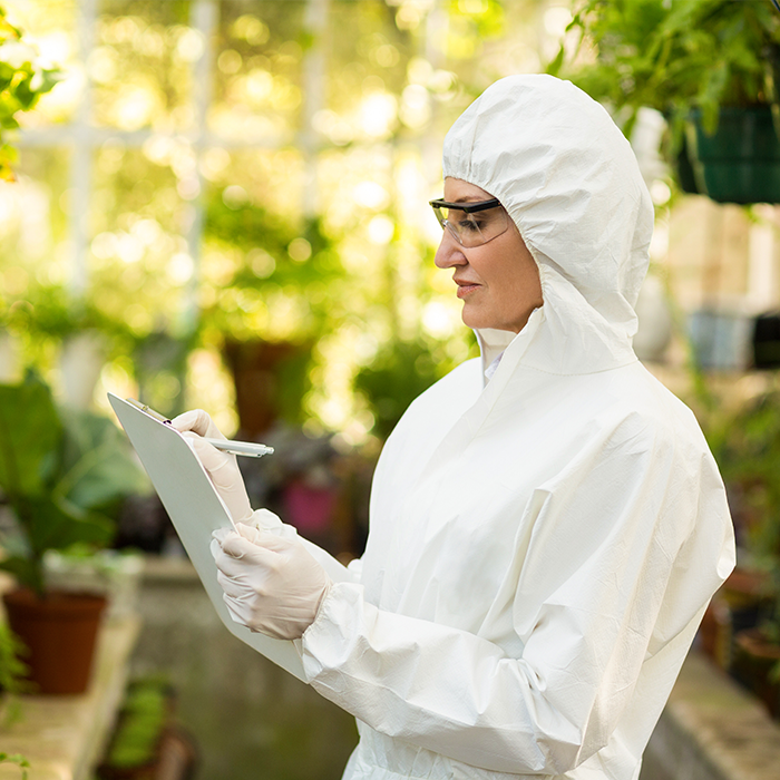 A green house worker wearing full body protective clothing.
