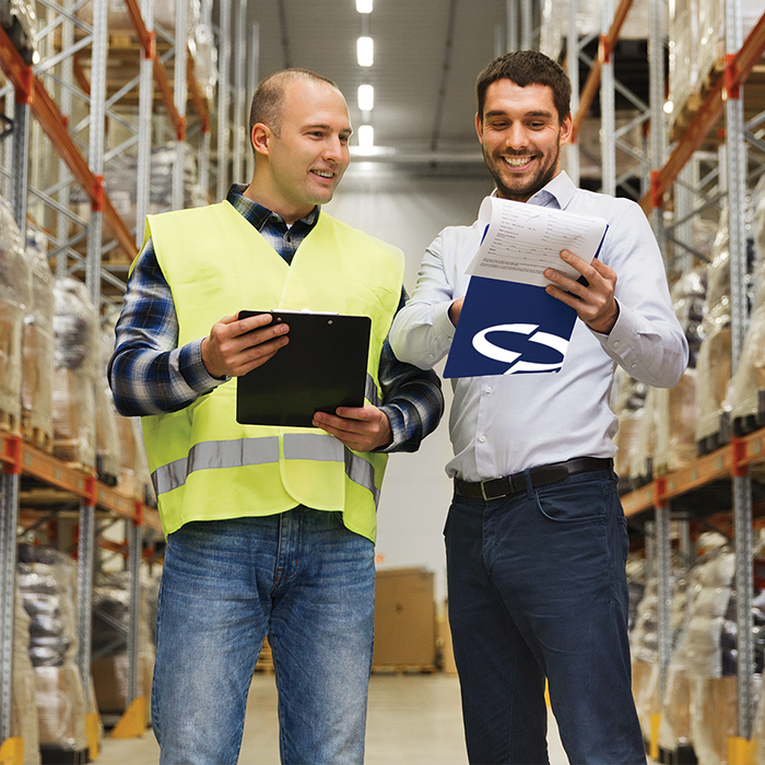 Two men discussing cost effective packaging options in an industrial warehouse with clipboards.