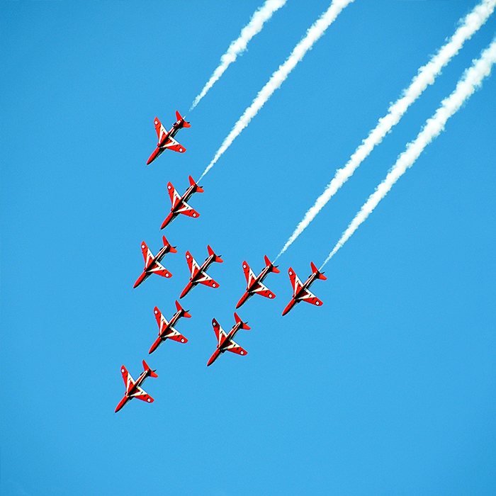 Red Planes in Blue Sky Performing Air Show