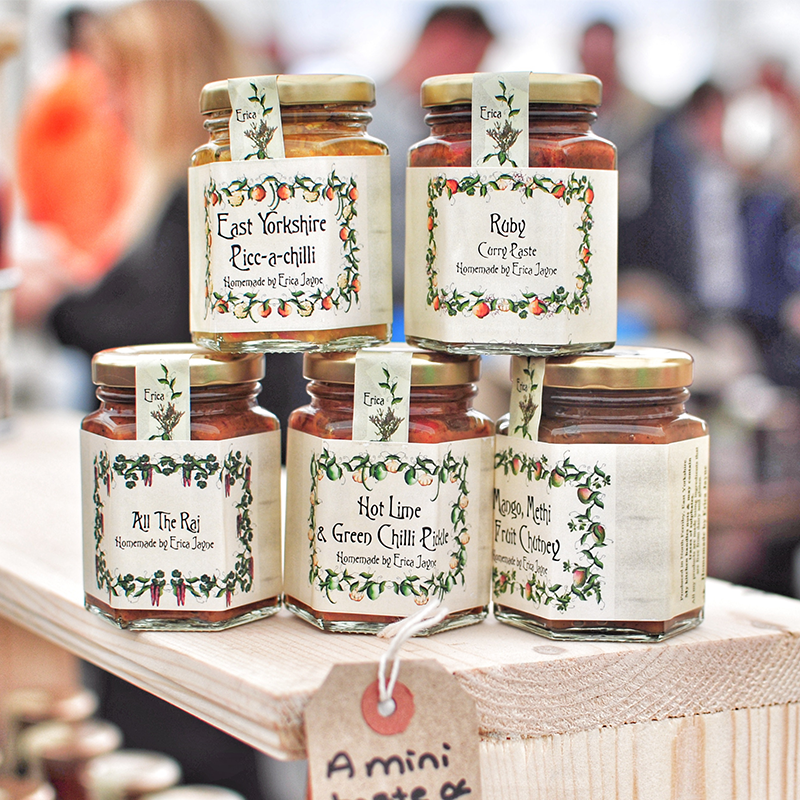 variety of jams and spreads at farmers market on wooden plank