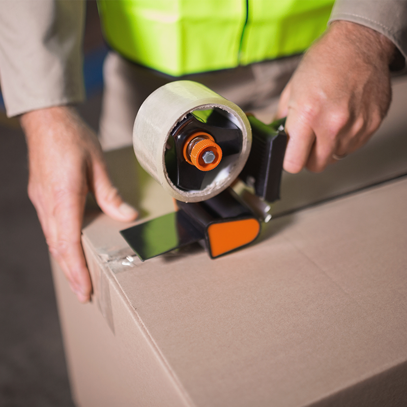 hands of a man holding hand tape gun taping box in warehouse facility