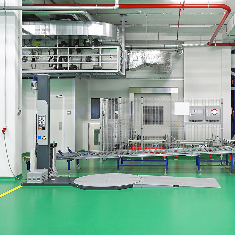 turntable stretch wrapper in manufacturing facility with green floor