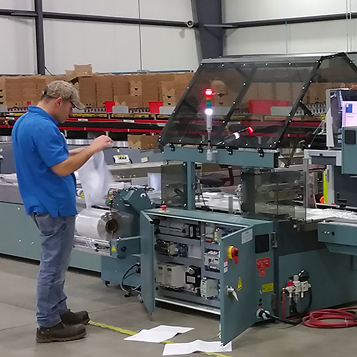 photo of service technician fixing shrink wrap machine in warehouse facility