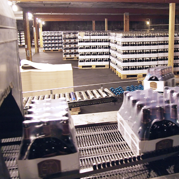 shrink wrapped cardboard trays of wine on conveyor in packaging facility