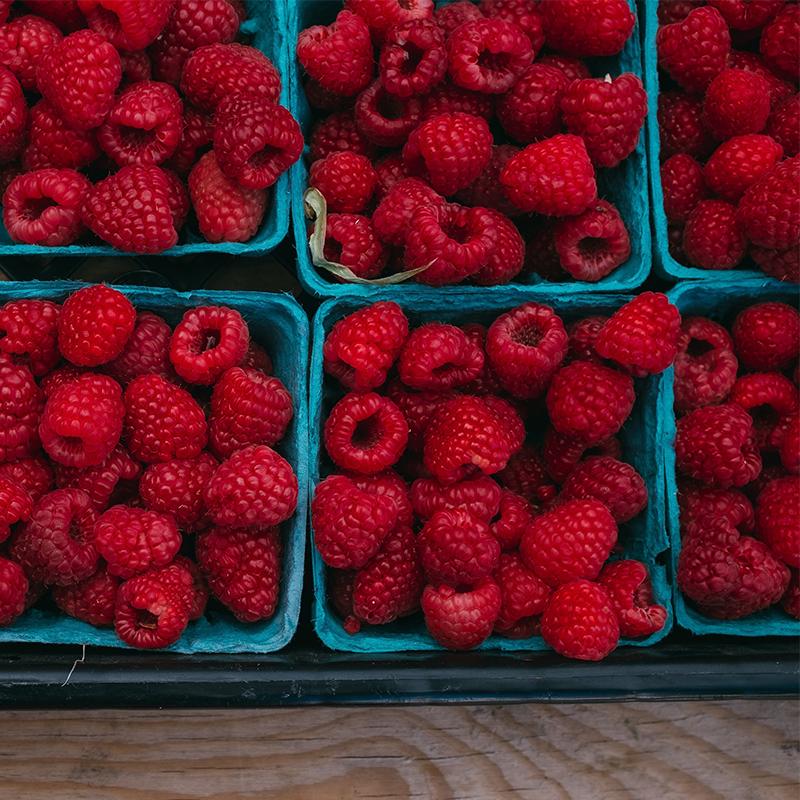 raspberries in blue fiber trays inside plastic flat on market shelf