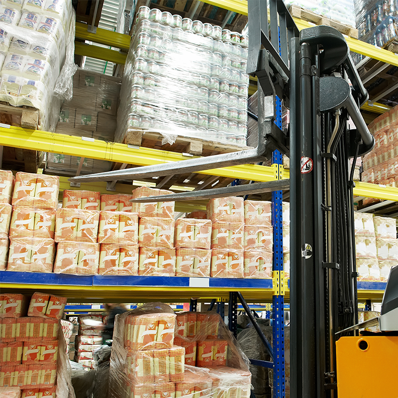 forklift in front of warehouse shelf filled with food products