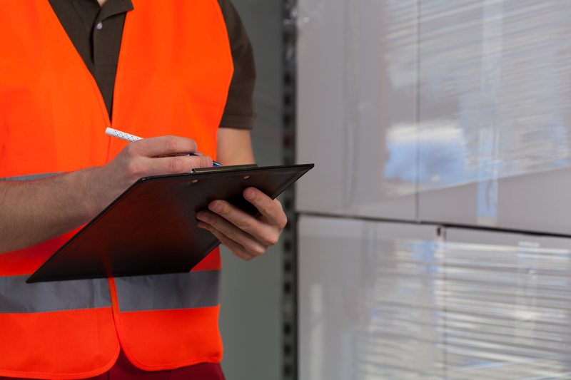 photo of man wearing reflective vest holding clipboard standing infront of stretch wrapper