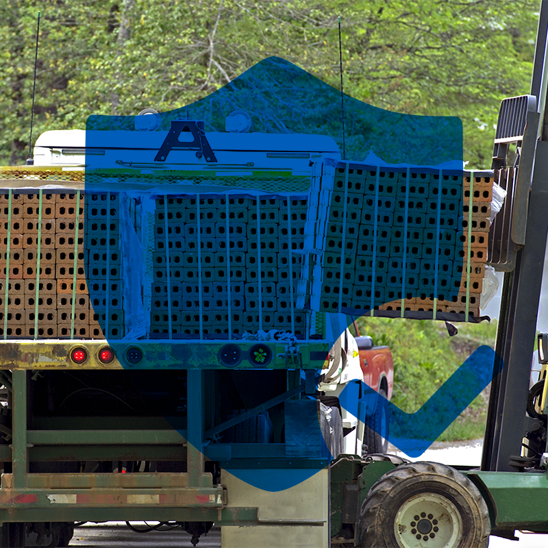 blue shield icon on top of photo of loads of bricks being unloaded with forklift