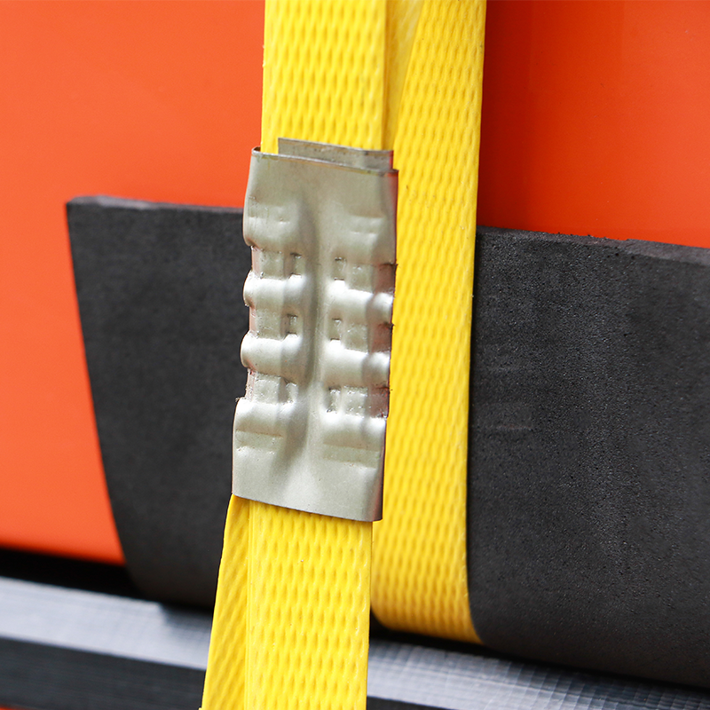 close up photo of yellow steel strapping securing large orange product