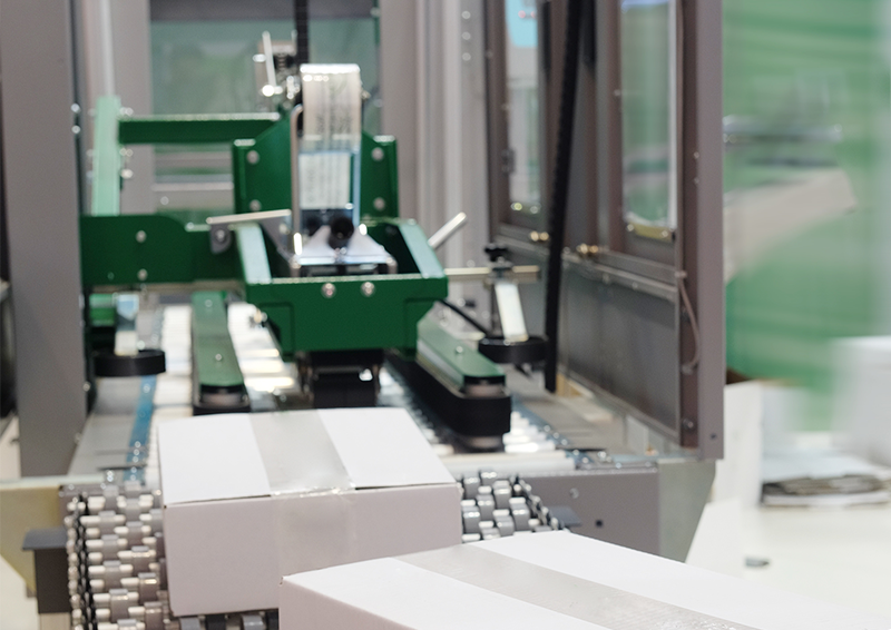 photo of an automatic case sealing system with a flexible conveyor moving white cardboard boxes