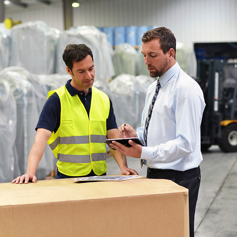 man holding clipboard wearing dress shirt talking to man wearing reflective vest in warehouse facility
