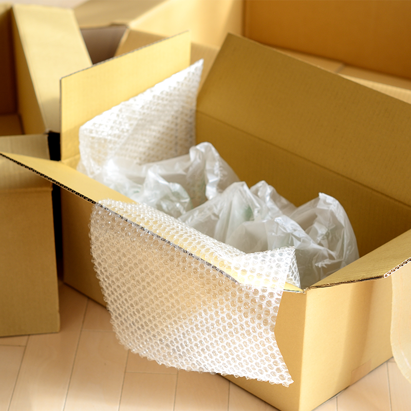 open cardboard box on floor filled with bubble wrap and air pillows