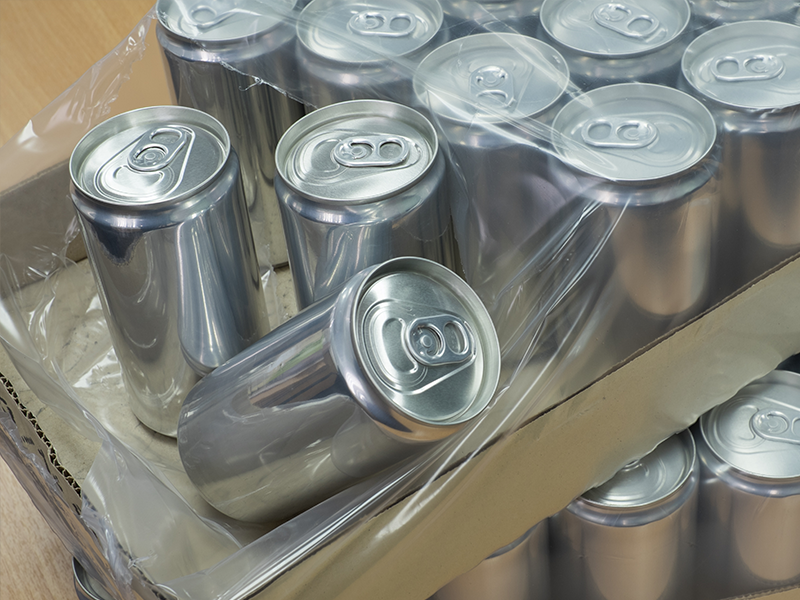 cardboard tray filled with plain aluminum cans wrapped in shrink wrap packaging