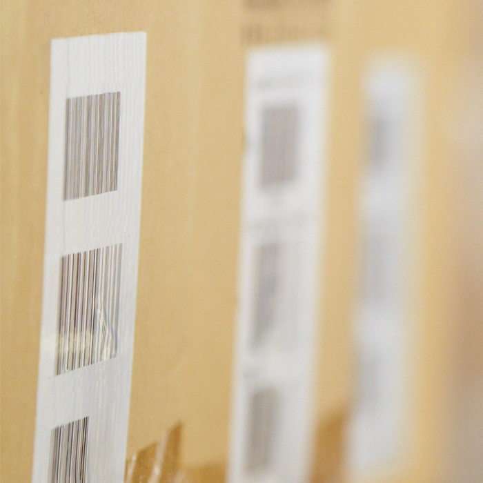 white barcode labels on cardboard boxes in a row of three