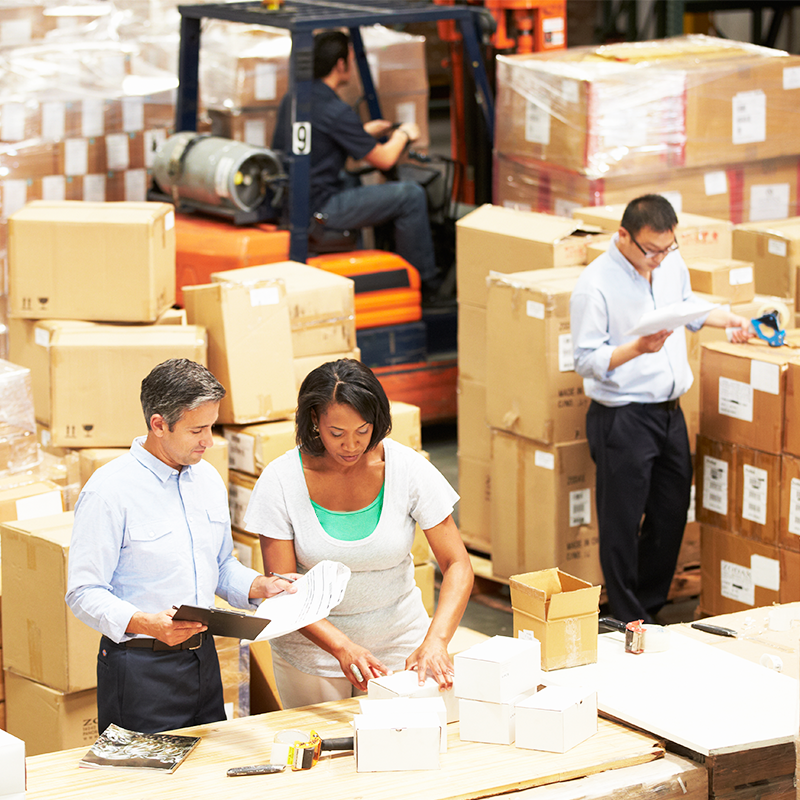 people working in warehouse surrounded by boxes in ecommerce fulfillment facility