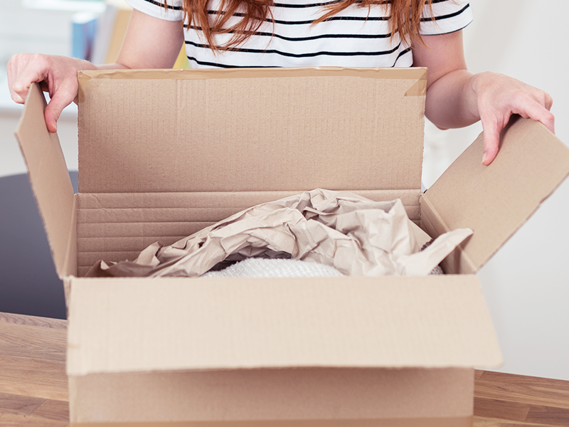 woman opening online order package filled with kraft paper and bubble wrap