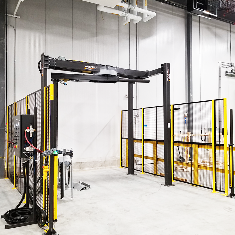 wulftec WRTA-175 rotary arm stretch wrapper with safety barriers inside logistics facility