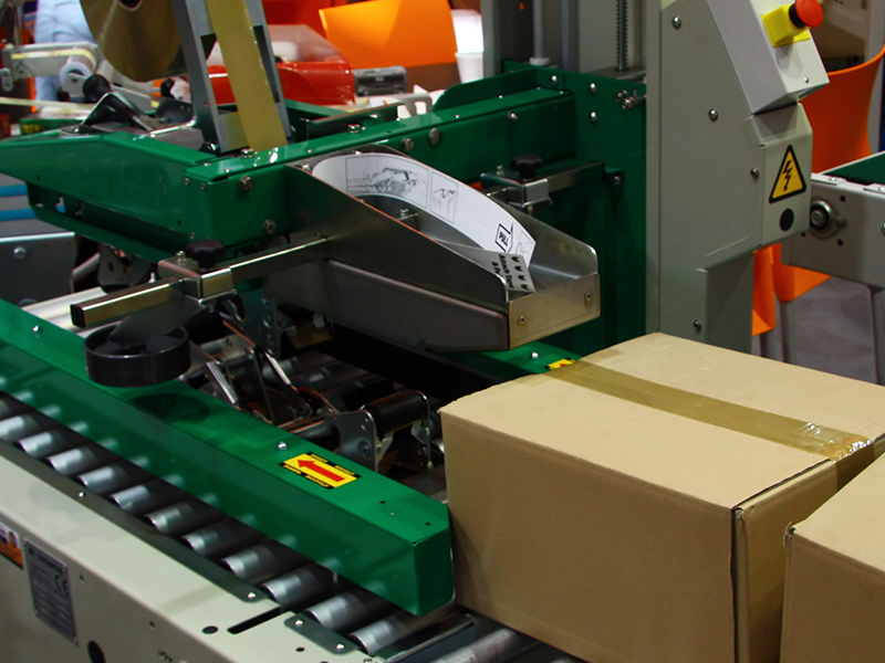 rubber adhesive tape being run through a green case sealing machine to pack boxes in packaging facility