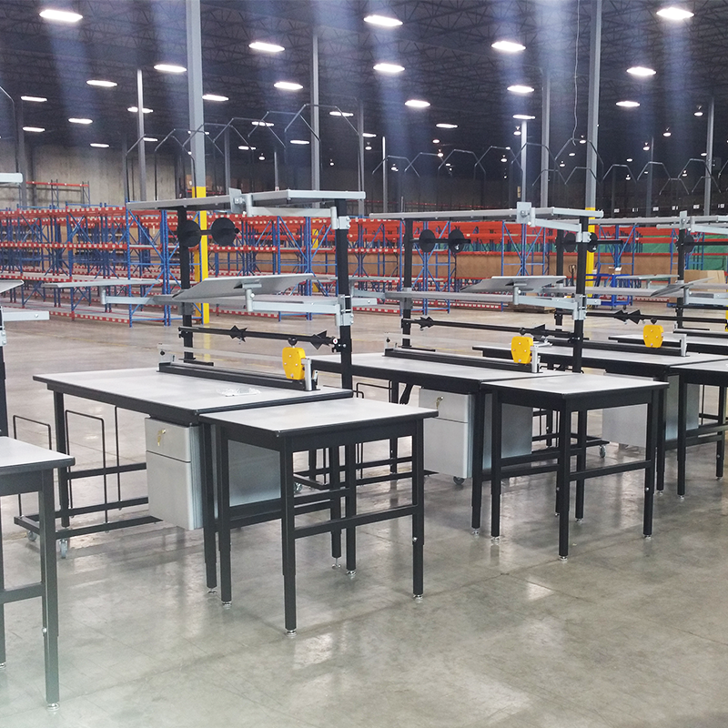 packaging stations in a row inside packaging facility near red and blue warehouse shelves