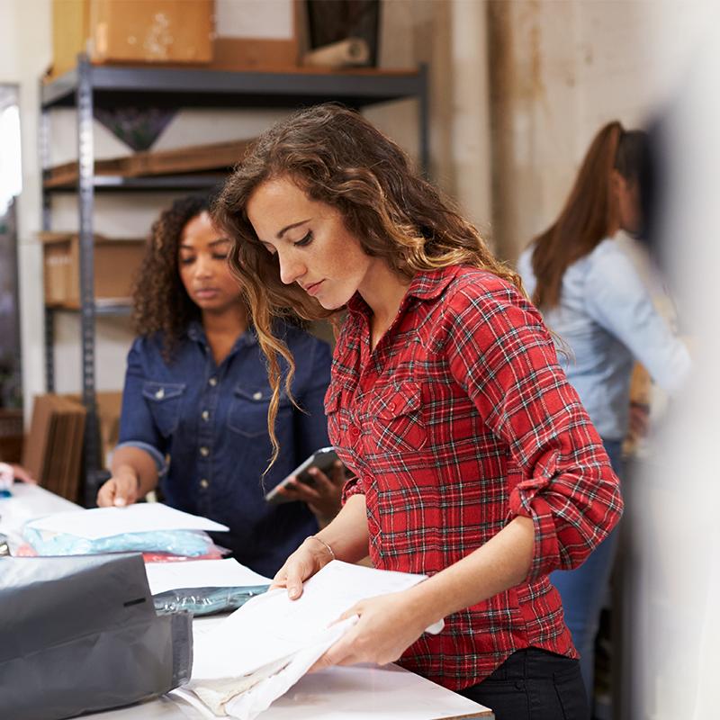 women packaging bags of apparel orders inside packaging facility