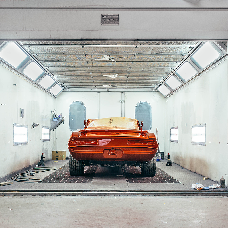 classic car freshly painted red in the paint booth at painting facility
