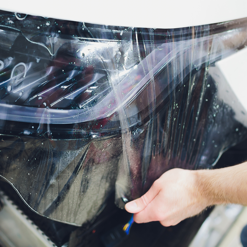 person applying protective polymask film to white car front bumper to protect paint