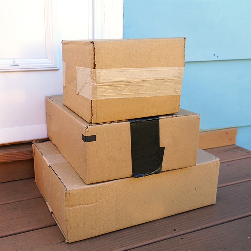 stack of three packages delivered to front door sealed with water activated tape