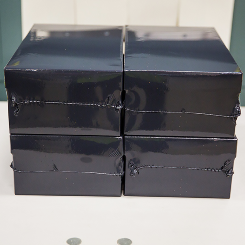 stack of four packages wrapped with black stealthwrap shrink film