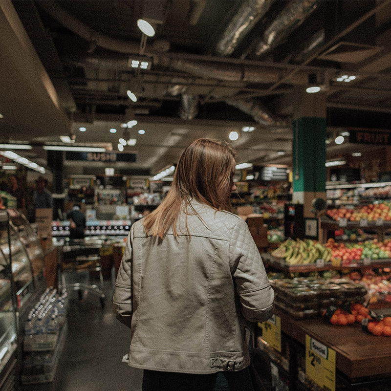 female consumer shopping at grocery store in produce section