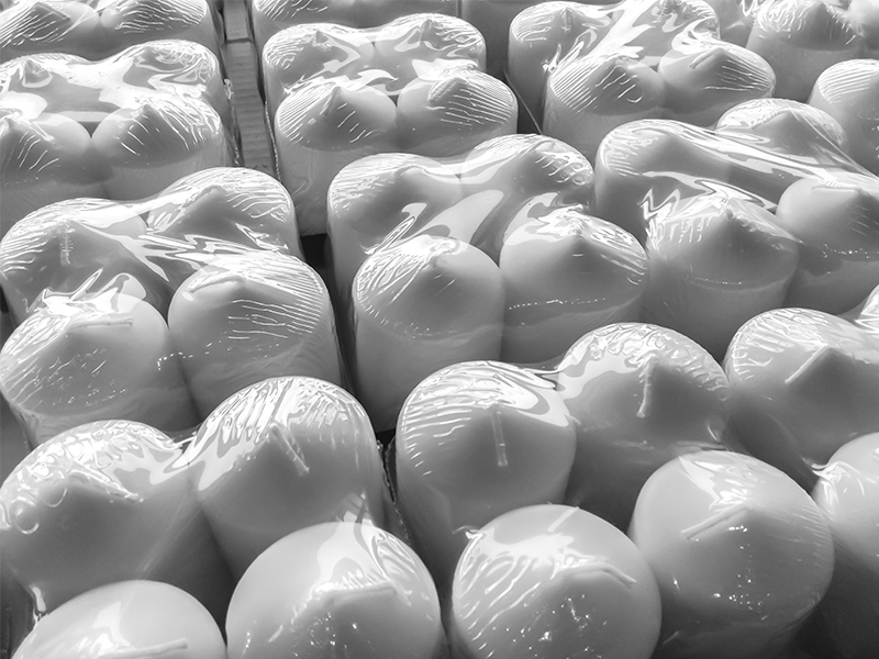 bundles of four white candles wrapped in clear shrink wrap film on conveyor system