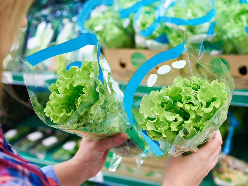 hands holding custom printed plastic bag with lettuce product in retail
