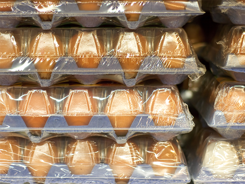 shrink wrapped egg cartons with brown eggs