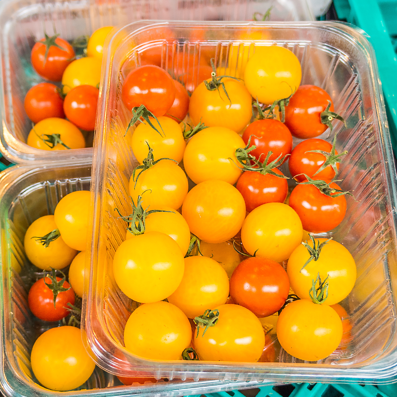 yellow and orange cherry tomatoes in aluminum tray with clear top seal film packaging