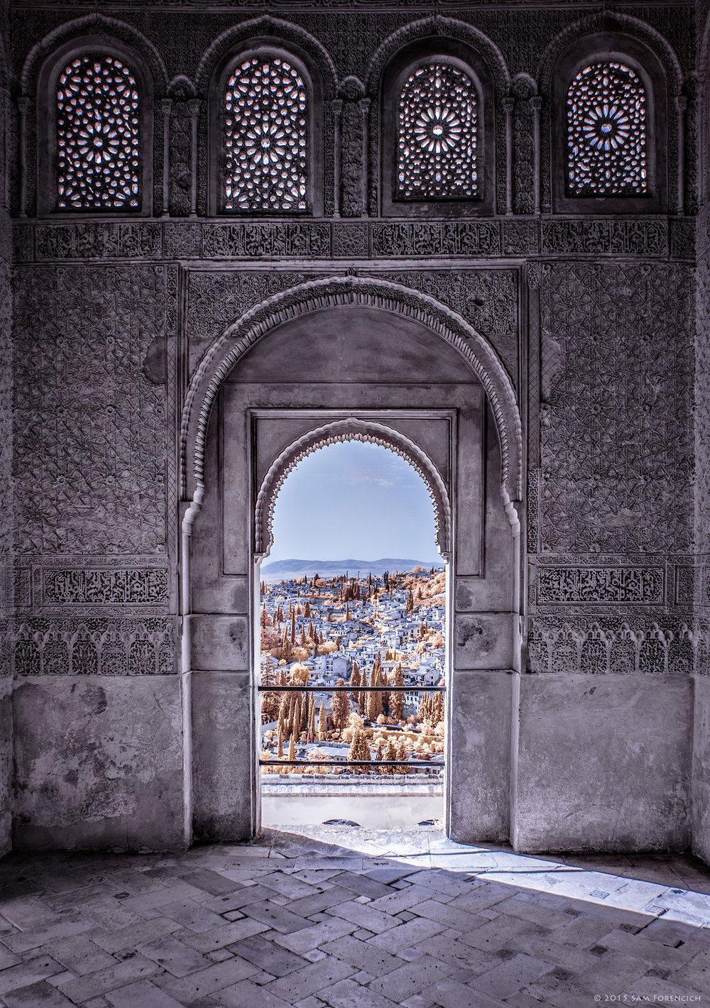 An arched passageway inside Moorish palace and fortress the Alhambra, frames a portion of the Andalusian city of Granada, Spain. The lavish ornamentation carved into the stucco consists largely of Arabic inscriptions manipulated into geometric patterns. Channel swapped infrared, IR converted Canon 5D Mark II.  ©2015 Sam Forencich