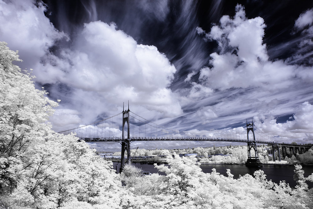 A spring storm breaks up over the St John's Bridge in Portland, Oregon. Completed in 1931, the St. Johns Bridge is a steel suspension bridge that spans the Willamette River in Portland, Oregon. Channel swapped infrared, IR converted Canon 5D Mark II.  © 2015 Sam Forencich