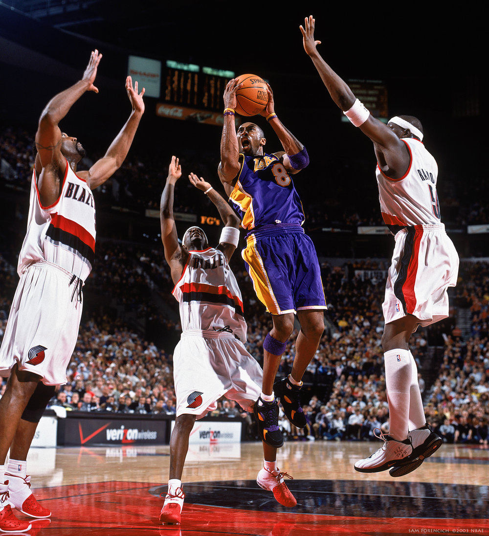 Portland, OR – Kobe Bryant #8 of the Los Angeles Lakers takes the ball up against Dale Davis #34, Jeff McInnis #5, and Zach Randolph #50 of the Portland Trail Blazers during an NBA game at the Rose Garden on December 13, 2003. Manually focused Hasselblad, RDP 100 film, arena strobe lighting.  Sam Forencich ©2003 NBAE